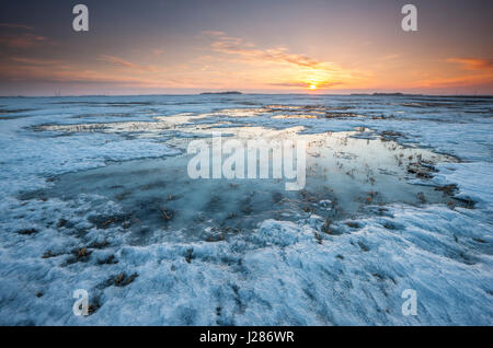 Sunset on frozen and snow covered fields in Manitoba, Canada - Stock Photo
