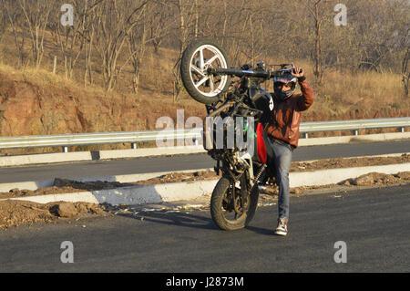 Stunt motorcycle rider performing at a local road near Pune, Maharashtra - Stock Photo