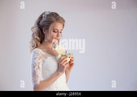 bride in wedding dress holding a chocolate Stock Photo