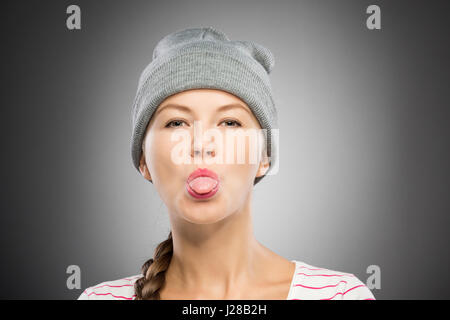 Attractive young woman in winter hat showing tongue - Stock Photo