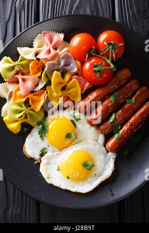 fried egg, sausages, pasta farfalle and tomato close-up on a plate. Vertical view from above - Stock Photo