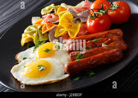 fried egg, sausages, pasta farfalle and tomato close-up on a plate. Horizontal - Stock Photo