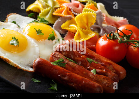 Delicious breakfast: fried egg, sausages, farfalle pasta and tomatoes close-up. Horizontal - Stock Photo