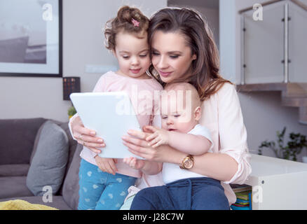 Portrait of a mother with children using a tablet - Stock Photo