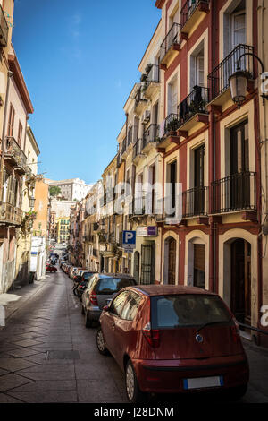Colorful houses in the narrow streets of Cagliari in Sardinia, Italy. Cars parked on the sideways. Beautiful blue - Stock Photo