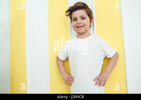 Little smiling boy in white t-shirt standing in baby room. Mock up. - Stock Photo
