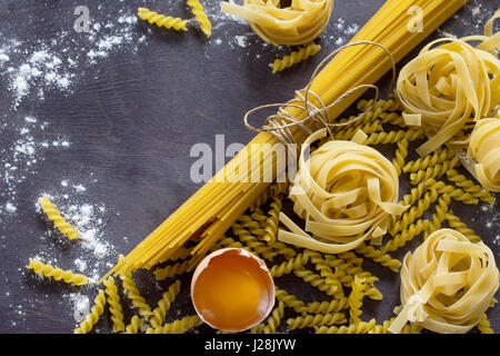 Various types of pasta spaghetti, fusilli, fettuccine and raw egg yolk on a kitchen wooden table. Copy space. - Stock Photo