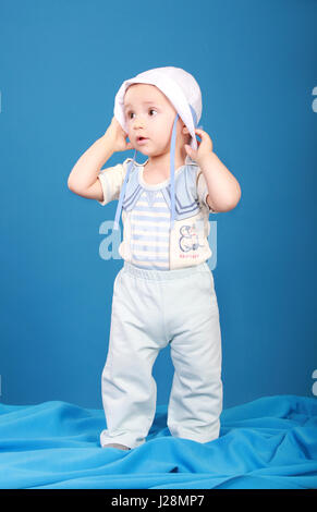 Little boy in sailor suit. Looking to the side, holding a hat in his hands - Stock Photo