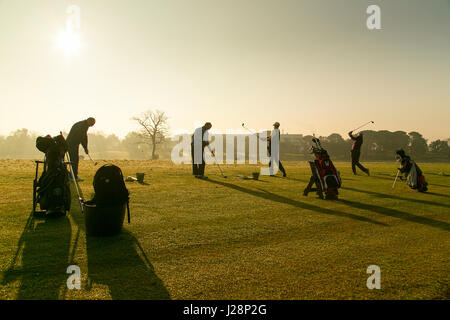 Golfers swinging golf clubs in early morning sun on practice driving range at dawn. - Stock Photo