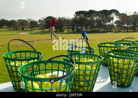 Golfers on practice range at dawn - Stock Photo
