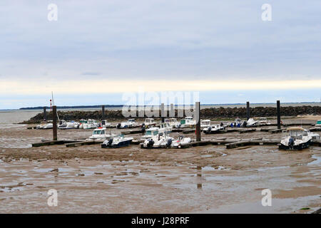 Fishing and leisure boats resting on the mud at low tide in Chatelaillon -plage, France - Stock Photo