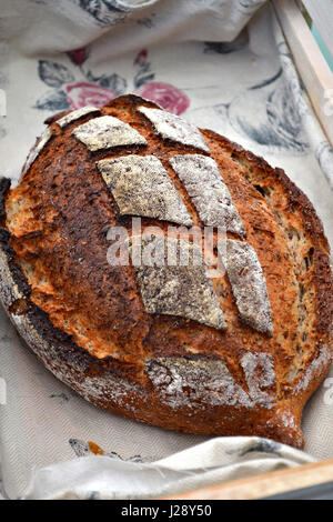 An artisanal bread in a rustic traditional bakery. A buttermilk and pumpkin seed loaf. - Stock Photo