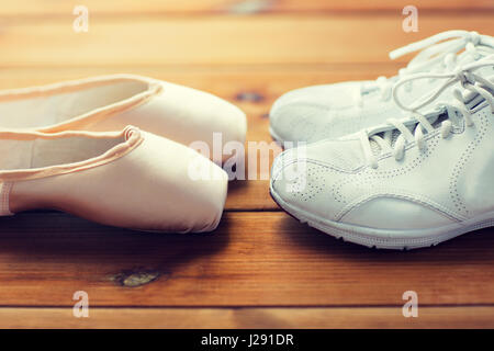 close up of sneakers and pointe shoes on wood - Stock Photo