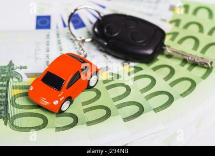 Car key with banknotes and key hanger in the form of a car   usage worldwide - Stock Photo