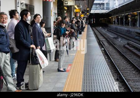 Tokyo, Japan - April 8th, 2017: Passengers waiting for the train at the Train Platform in Shinjuku station, Tokio. - Stock Photo