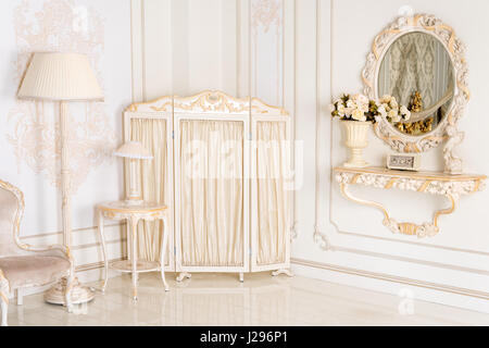 Luxury bedroom in light colors with mirror and folding screen. Elegant classic interior - Stock Photo