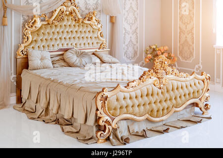 Luxury bedroom in light colors with golden furniture details. Big comfortable double royal bed in elegant classic - Stock Photo