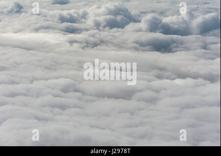 Grey cloud cover hovering low over valley seen from above with dramatic formations - Stock Photo