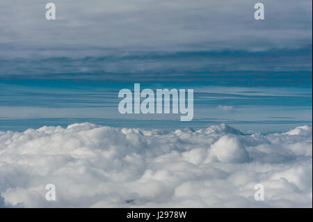 Grey cloud cover hovering low over valley seen from above with blue sky on horizon - Stock Photo