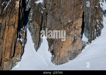 Two climbers scaling a large granite rockface in winter - Stock Photo