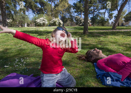 three years old blonde child, with red shirt, sitting on knees in green grass in park, next to mother sleeping, - Stock Photo