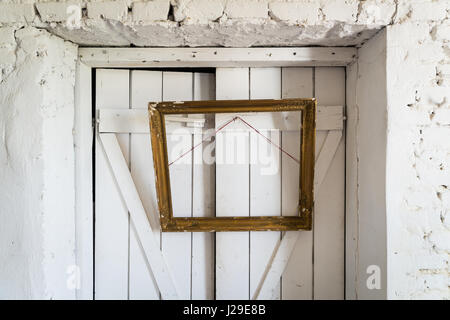 Old wooden painting frame hanging on the wooden doors - Stock Photo