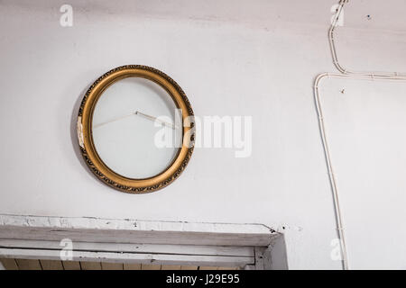 Old wooden empty oval painting frame on the white wall over the doors - Stock Photo