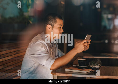 Young Asian man sitting in a cafe surfing the internet - Stock Photo