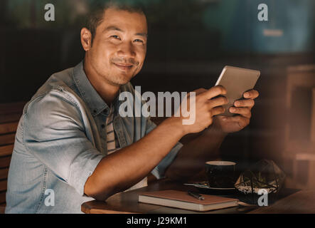 Content Asian man browsing online while sitting in a cafe - Stock Photo