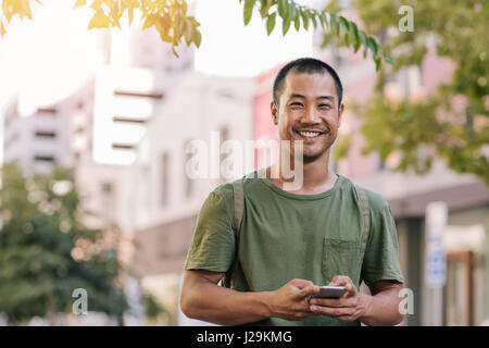 Young Asian man sending a text on his cellphone outside - Stock Photo