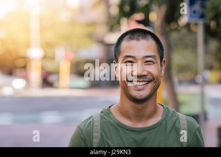 Young Asian man smiling confidently on a city street - Stock Photo
