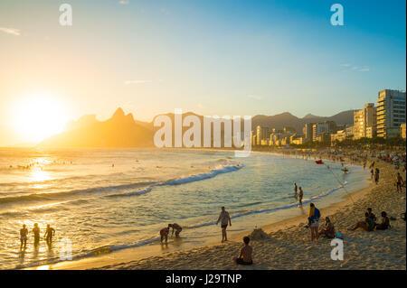 RIO DE JANEIRO - FEBRUARY 14, 2017: Visitors gather at the Arpoador end of Ipanema Beach to watch the sun set behind - Stock Photo
