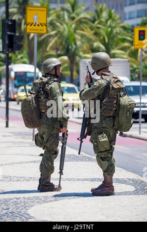 RIO DE JANEIRO - FEBRUARY 15, 2017: Two army soldiers in full camouflage uniforms stand with rifles on Copacabana - Stock Photo