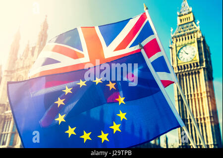 UK and EU European Union flags flying together in bright sun in front of the Houses of Parliament at Westminster - Stock Photo