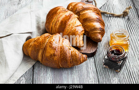 Croissants bakery, french buttery pastry with ham jars on wooden background - Stock Photo