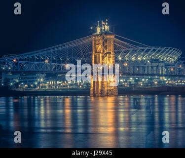 Cool blue image of the John A. Roebling suspension bridge and Paul Brown Stadium located in Cincinnati, Ohio. - Stock Photo