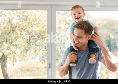 Toddler boy on father's shoulders at home by window - Stock Photo