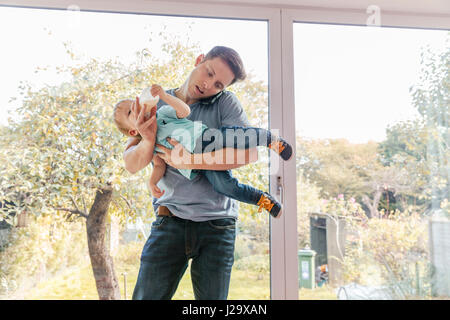 Father holding toddler son while on phone at home, by window - Stock Photo