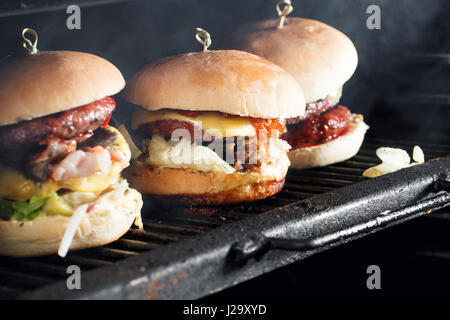 Delicious burgers with beef, tomato, cheese and lettuce. cooked on the grill assembled. heat the grill and the smoke - Stock Photo