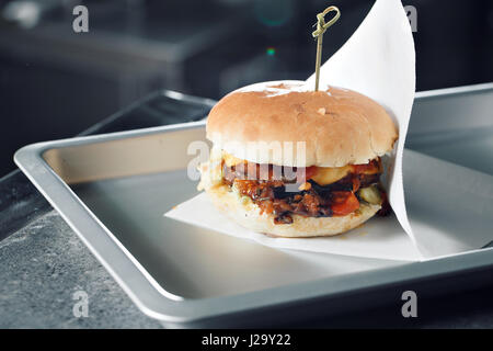 Delicious burgers with beef, tomato, cheese and lettuce. cooked on the grill assembled. - Stock Photo