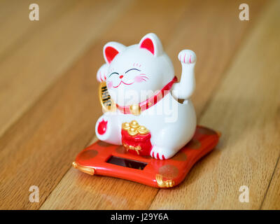 A maneki-neko (literally, 'beckoning cat' in Japanese, also known as a lucky cat, Chinese lucky cat, or happy cat) - Stock Photo