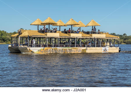 A party of tourists from Zambia enjoying a cruise on the Zambezi River in a uniquely designed catamaran close to - Stock Photo