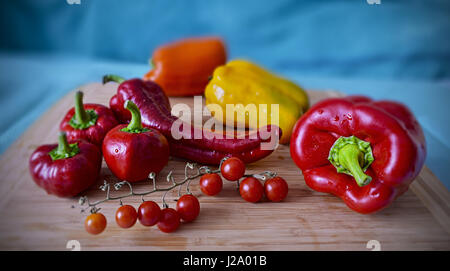 fresh ripe red yellow orange peppers and cherry tomatoes, home grown autumn harvest - Stock Photo