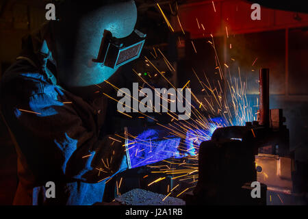 Worker is welding steel part in factory - Stock Photo
