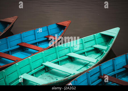 Colourfully painted wooden canoes lined up by the lakeside in Pokhara, Nepal. - Stock Photo