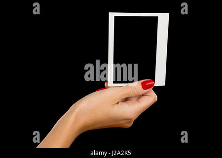 Close up of woman's hand with red nails holding blank polariod photo. Studio shot on black background. - Stock Photo