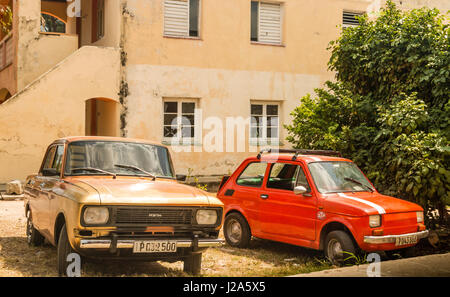 Old classic cars parked outisde house, Cuba - Stock Photo