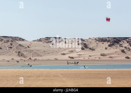 Africa, Western Sahara, Dakhla. Kite surfers in a bay of the Atlantic Ocean. - Stock Photo