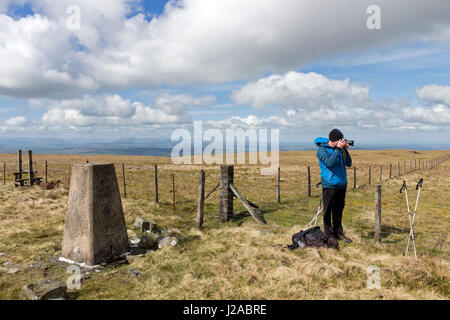 Walker at the Trig Point on the Summit of Black Fell in the North Pennines and the view towards the Mountain of - Stock Photo