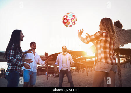 Group of happy young people playing with ball on beach in summer - Stock Photo